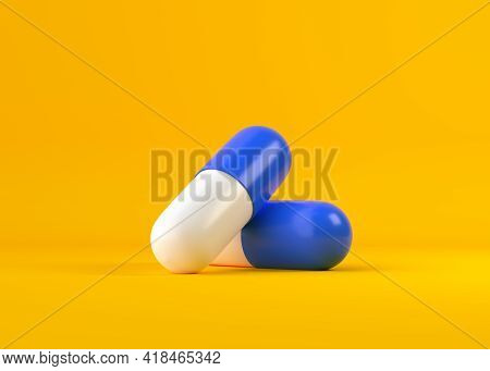 Two Blue-white Pill Capsules Over Yellow Background, Medical Treatment, Pharmaceutical Or Medication