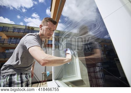 Man Cleaning Window With Rag At Home. Themes Housework And Housekeeping.