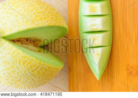 Closeup To Split The Yellow Galia Melon On Wood Plate