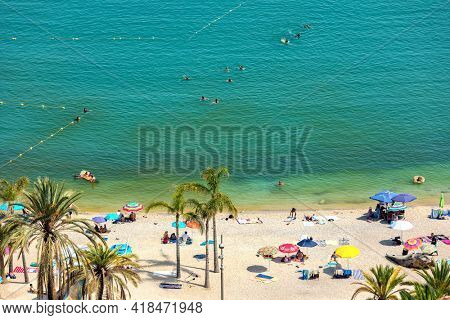 MENTON, FRANCE - JULY 31, 2020: People on the public beach on sunny summer day in Menton - small town on Mediterranean sea,  famous travel destination and tourist resort on French Riviera.
