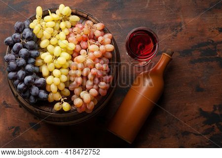 Wine bottle, grapes, glass of red wine and old wooden barrel. Top view