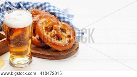 Lager beer mug and fresh baked homemade pretzel with sea salt on wooden table. Classic beer snack. With copy space
