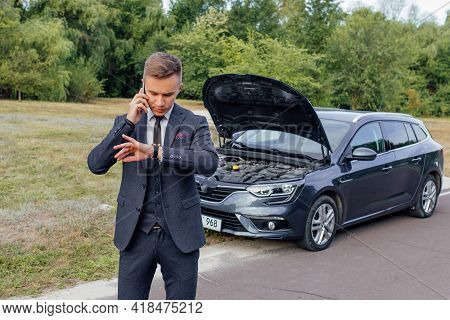 Portrait Of Stressed Young Man Calling On Cellphone For Service His Breakdown Car. Serious Caucasian