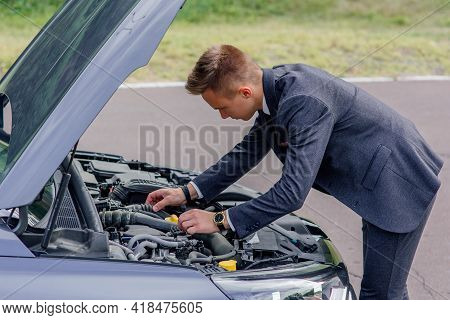 Young Man Looking Under The Hood Of Breakdown Car. Car Breakdown. Side View Of Concentrated Young Ma