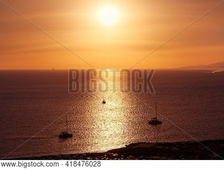 Superb Sunset Seascape. Low Sun In Hazy Sky, Sun Glare On Sea Waters. Small Sailboats, Sunlight Stri