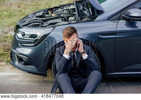 Upset Young Man Use Phone Sitting On Road Near The Broken Car Opened The Hood Help Repair Stress Pro