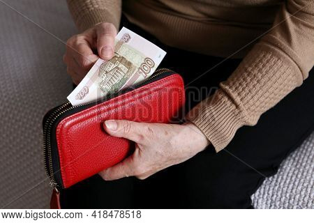 Elderly Woman Takes Out Russian Rubles From Her Wallet, Wrinkled Female Hands Closeup. Concept Of Po