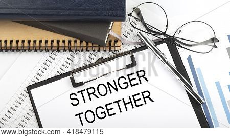 Text Stronger Together On Office Desk Table With Notebooks, Supplies,analysis Chart, On White Backgr