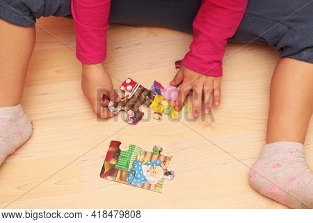 A Child Girl Plays Collects Jigsaw Puzzles At Home, In Kindergarten Or In A Nursery. A Little Girl P