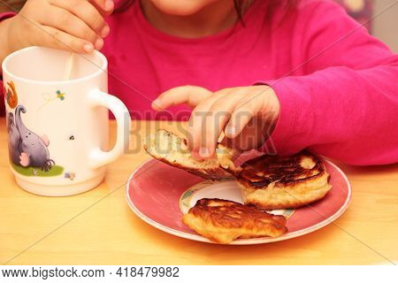 A Little Girl Eats Pancakes For Breakfast And Drinks Milk From A Beautiful Cup. Healthy Baby Food.