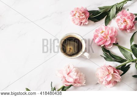 Feminine Floral Composition. Cup Of Coffee And Pink Peonies Flowers On White Marble Table Background