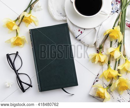 Cup Of Coffee With Beautiful Narcissus Flowers And Book On White Table. Top View. Reading Concept.