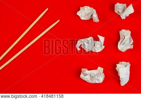 Chopsticks And Crumpled Scraps Of White Paper On A Red Background. Six Pieces Of Crumpled Paper And