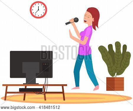 Woman Holding Microphone And Singing Music In Karaoke. Girl Stands With Mike Next To Tv At Home. Sin