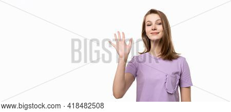 Friendly Girl Saying Hello, Smiling Joyfully And Friendly, Waving Her Hand, Showing Five Fingers, Fr