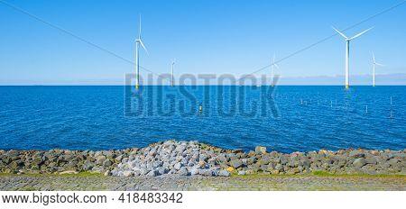 Wind Turbines For Renewable Energy In A Lake In Bright Blue Sunlight In Spring, Noordoostpolder, Fle