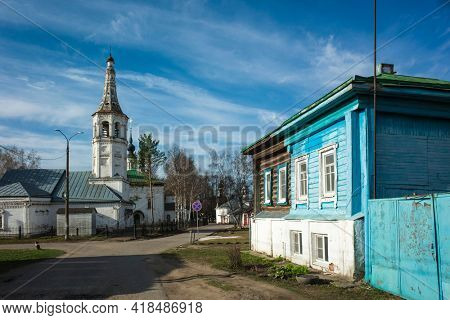 Street of Suzdal, Old wooden traditional russian house half painted blue and Sorrowful (Skorbyashchenskaya) Church in sunny spring day middle april, Ancient Russian architecture, Golden Ring of Russia