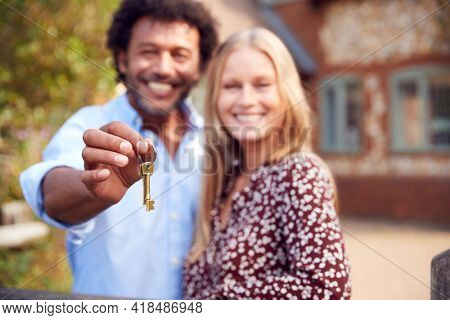 Portrait Of Excited Couple By Gate Holding House Keys Outside New Home In Countryside On Moving Day