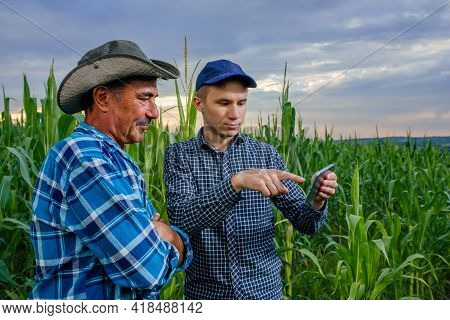 Farming Industry Of Two Farmers Using A Tablet Pc, Front View On Modern Farmers With Digital Tablet,