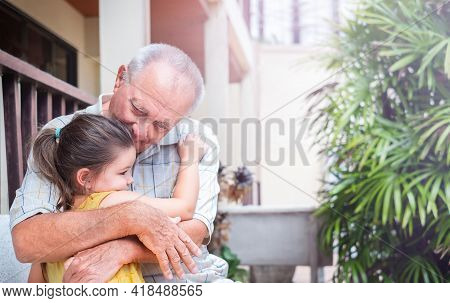 Retired Senior With Child Outdoors. Grandfather Hugs Granddaughter On A Walk