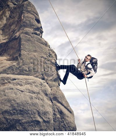 businessman climbing on mountain with rope and backpack