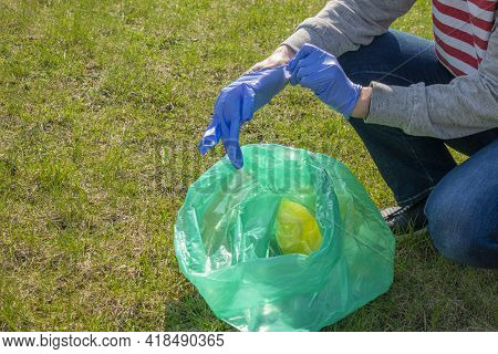 Woman Cleaning Up Nature Of Garbage. Volunteer Putting On Blue Gloves And Picking Trash Into Plastic