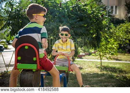 Two Little Brother Toddlers Playing With Swing Balancer
