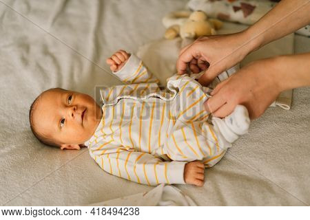 Mom Dresses Cute Newborn Little Baby Boy In A  Jumpsuit. Happy Young Mother Playing With Baby While