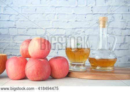 Apple Vinegar In Glass Bottle With Fresh Green Apple On Table