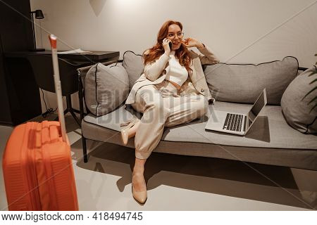 Young Businesswoman Work At Hotel. Business Trip Concept. A Very Busy Red-haired Female Model In A S