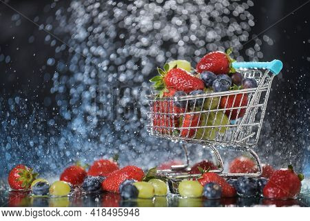 Close Up Of Blue Shopping Box With Fruit Salad. Blue Shopping Cart With Red Strawberry, Green Grape,