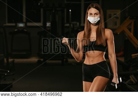 A Fit Woman In A Face Mask To Avoid The Spread Of Coronavirus Is Doing Bicep Curls With Dumbbells. A
