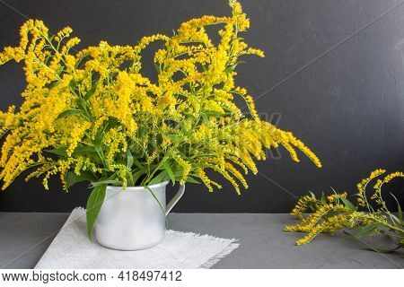 Bouquet Of Canadian Goldenrod In An Aluminum Mug On A Linen Napkin On A Gray Background, Twigs With