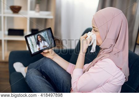 Sick Muslim Woman Patient Suffering From Cold, Covid And Running Nose, Sitting On Sofa At Home, Talk