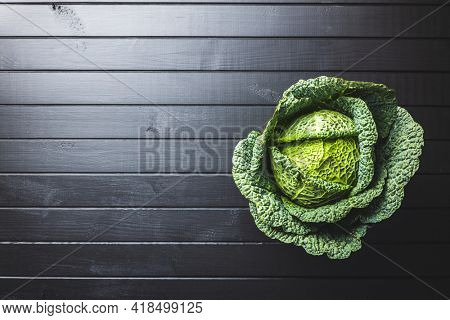 Green savoy cabbage on wooden table. Top view.