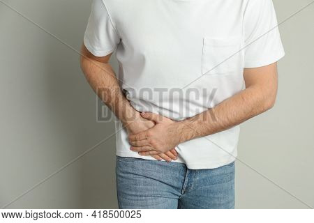 Man Suffering From Acute Appendicitis On Light Grey Background, Closeup