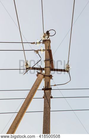 Electricity Concept, Concrete Pole With High Voltage Wires On Insulators. Close-up Against The Blue