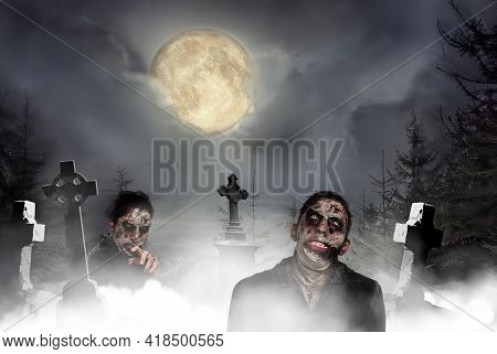 Scary Zombies At Misty Cemetery With Old Creepy Headstones Under Full Moon. Halloween Monsters