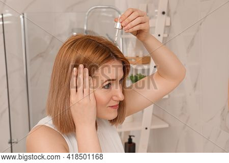 Woman Applying Oil Onto Hair At Home. Baldness Problem