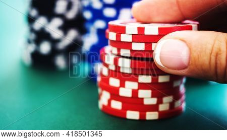 Stack of red casino chips in gambler hand