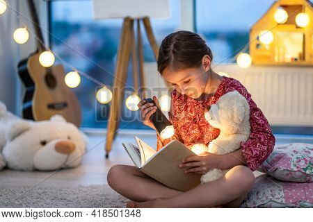 Beautiful brown hair toddler girl reads a book with flashlight in the bedroom. Child sitting with Teddy bear and fairy tale before bedtime. Christmas lights in children bedroom