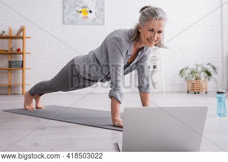 Happy Mature Woman Practicing And Watching Yoga Tutorial On Blurred Laptop.