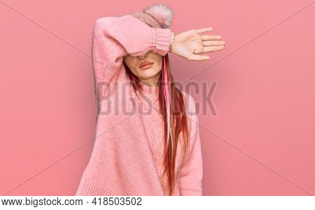 Young caucasian woman wearing casual clothes and wool cap covering eyes with arm, looking serious and sad. sightless, hiding and rejection concept