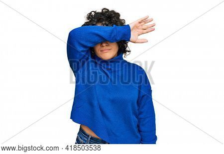 Young hispanic woman with curly hair wearing turtleneck sweater covering eyes with arm, looking serious and sad. sightless, hiding and rejection concept