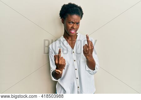 Young african american girl wearing casual clothes showing middle finger doing fuck you bad expression, provocation and rude attitude. screaming excited