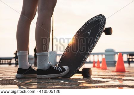 Asian Woman Leg On Surf Skate Or Skate Board In Outdoor Park At Sunset. Sport Training For Trendy Pe