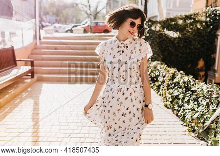 Graceful Short-haired Girl In Wristwatch And Sunglasses Walking Around City In Summer Day. Outdoor P