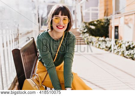 Laughing Elegant Woman Chilling After Spring Walk. Outdoor Photo Of Lovely Brunette Lady Sitting On