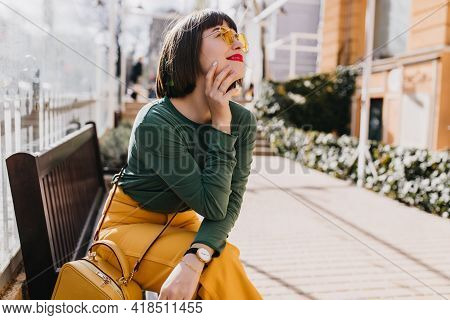 Attractive Brown-haired Girl In Green Sweater Chilling On Bench. Outdoor Portrait Of Gorgeous Lady I