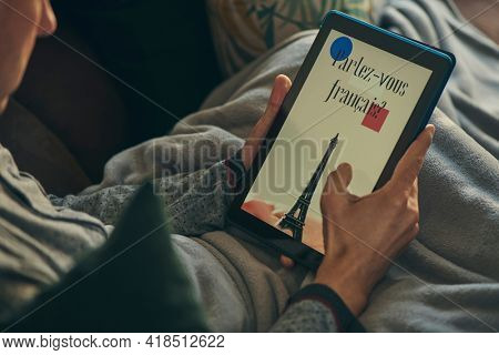 closeup of a young caucasian man, lying comfortably in a sofa wrapped in a warming gray blanket, watching at his tablet, that reads do you speak french written in french